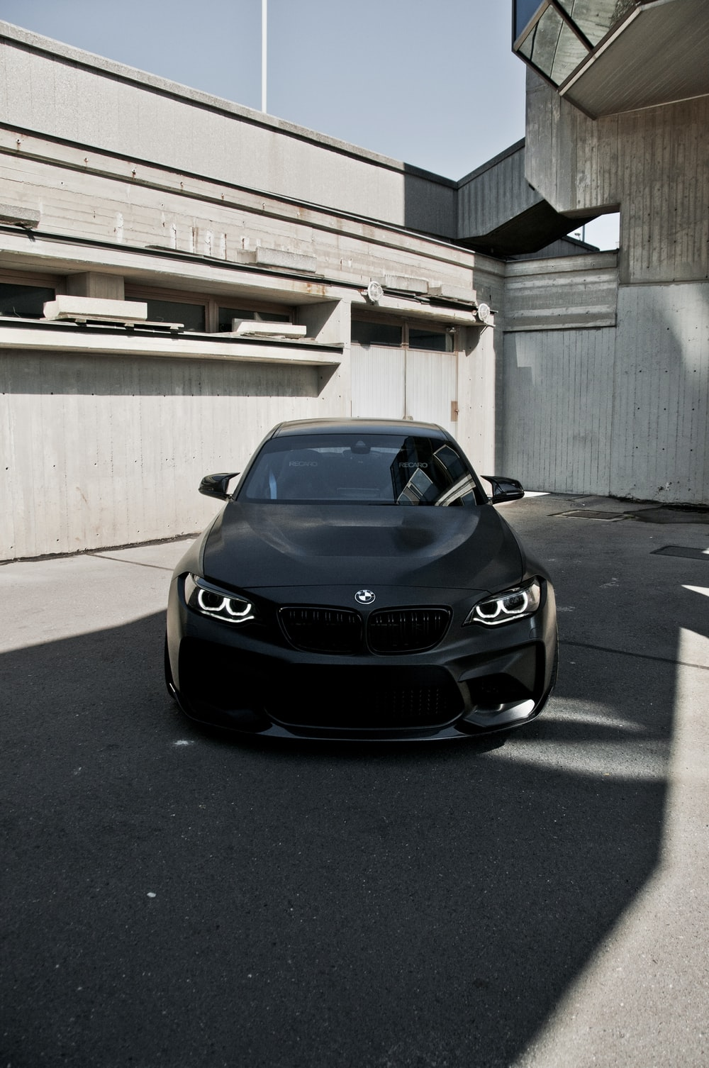 black bmw car parked on gray concrete floor during daytime