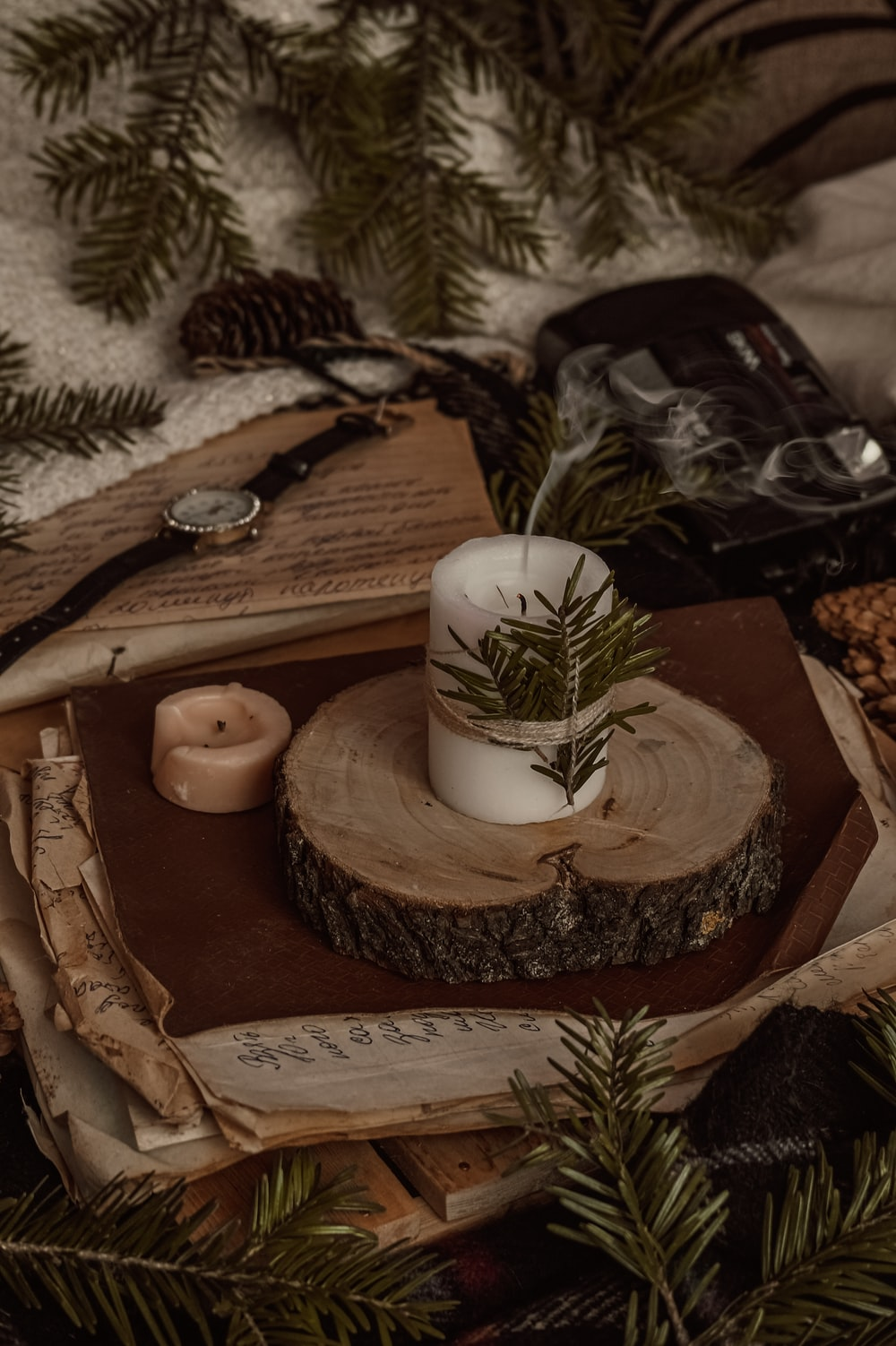 white pillar candle on brown wooden tray