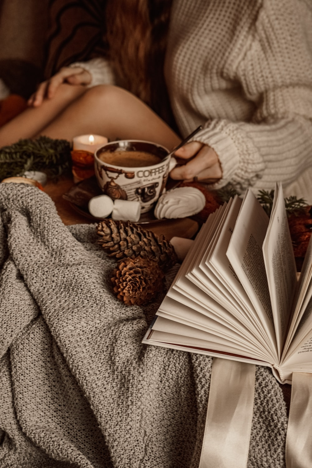 woman in gray sweater reading book