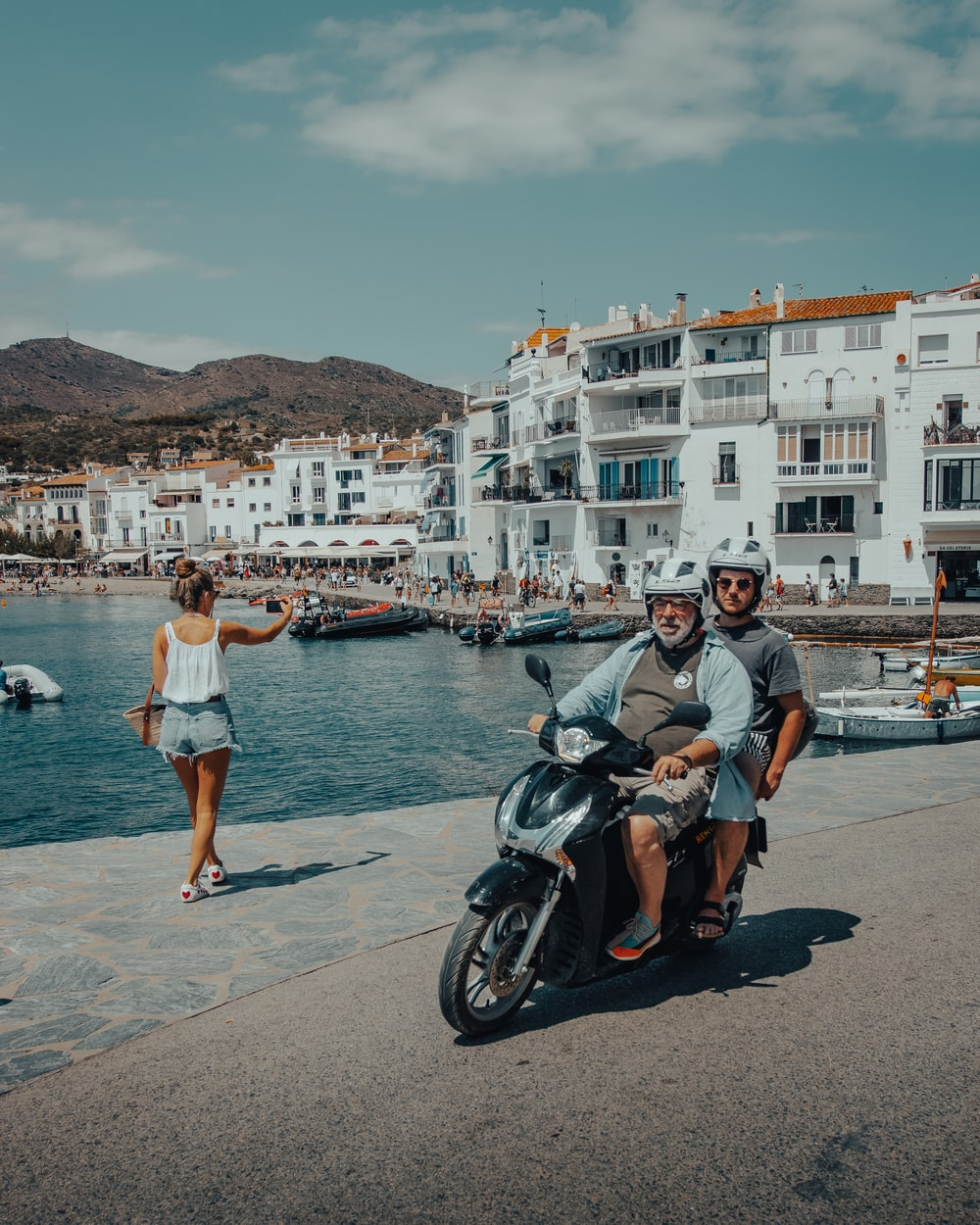 man and woman standing beside black motorcycle near body of water during daytime
