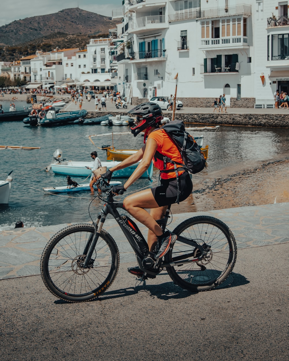 woman in black and orange shirt riding on bicycle near body of water during daytime