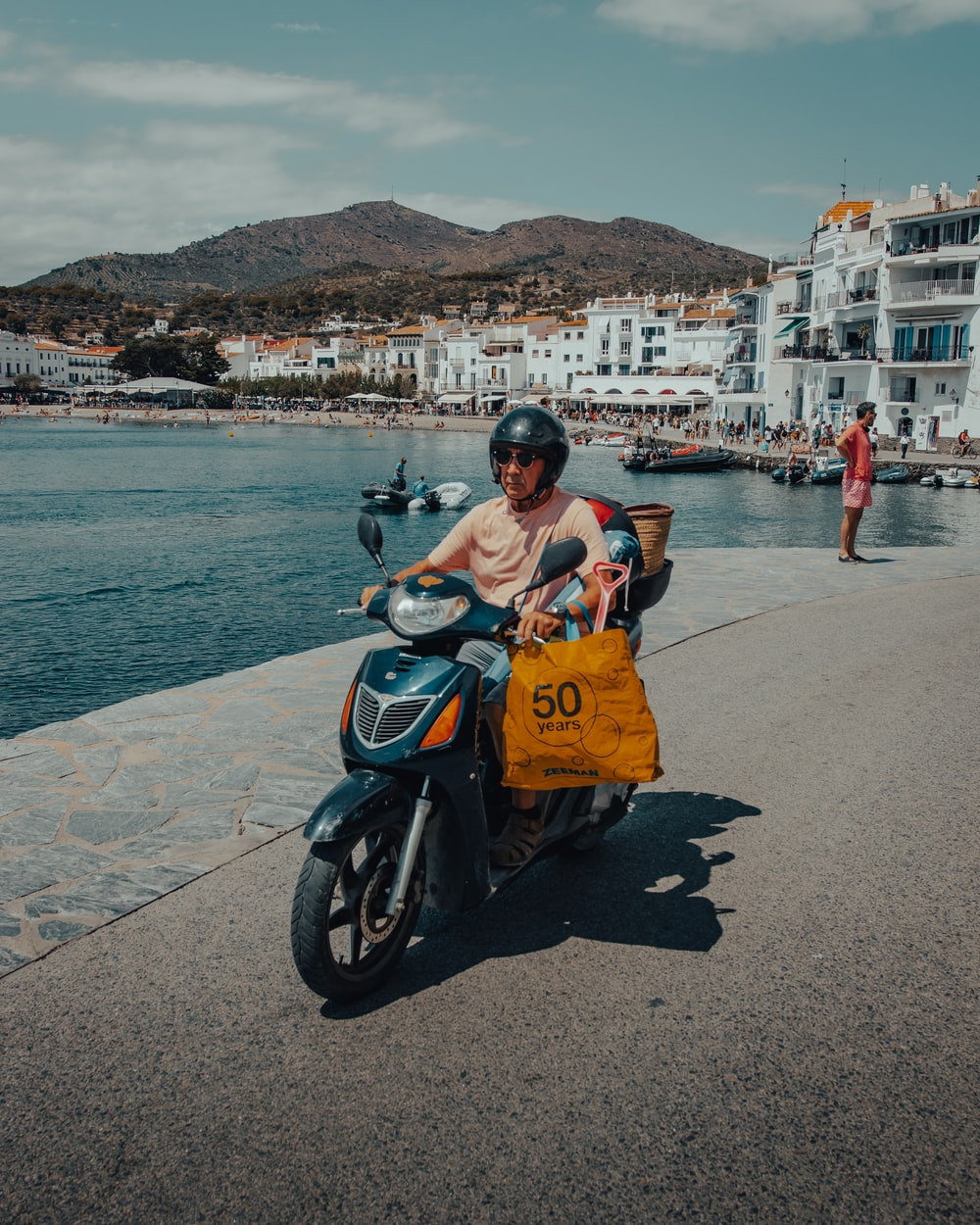 woman in orange dress sitting on black motor scooter near body of water during daytime