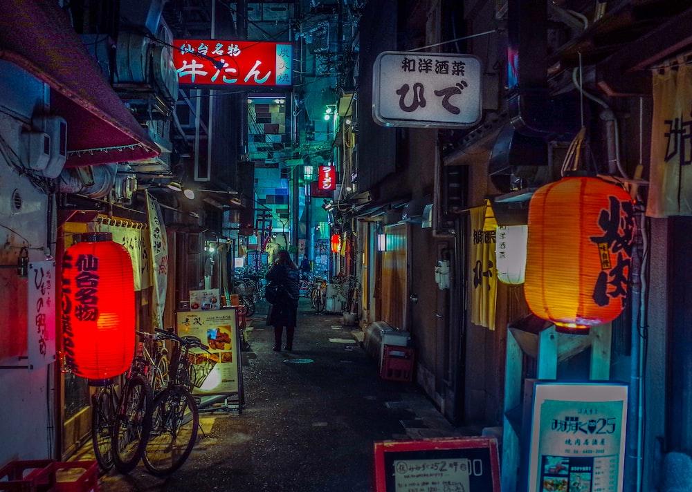 man in black jacket walking on sidewalk during nighttime