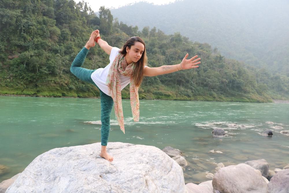woman in white long sleeve shirt and blue denim jeans standing on rock near body of near near near near
