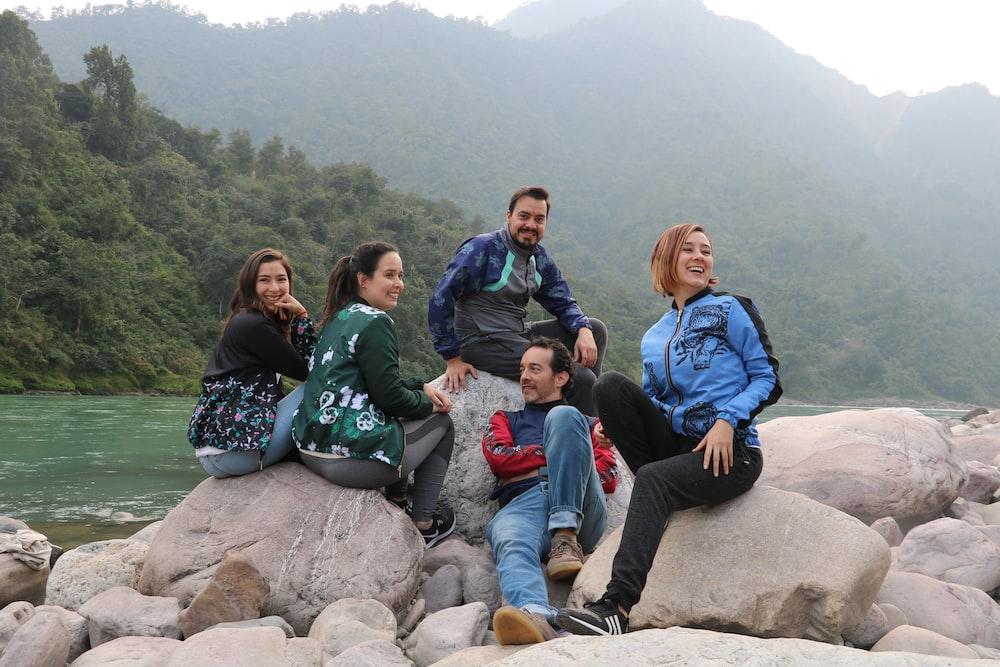4 women sitting on rock