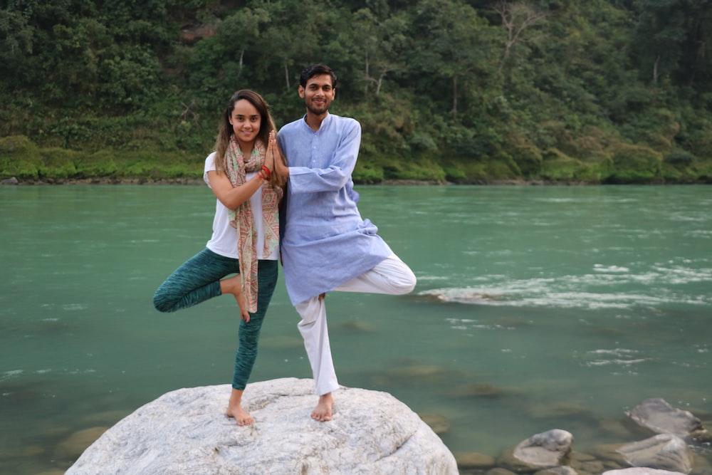 woman in white long sleeve shirt standing beside woman in blue denim jeans on white rock