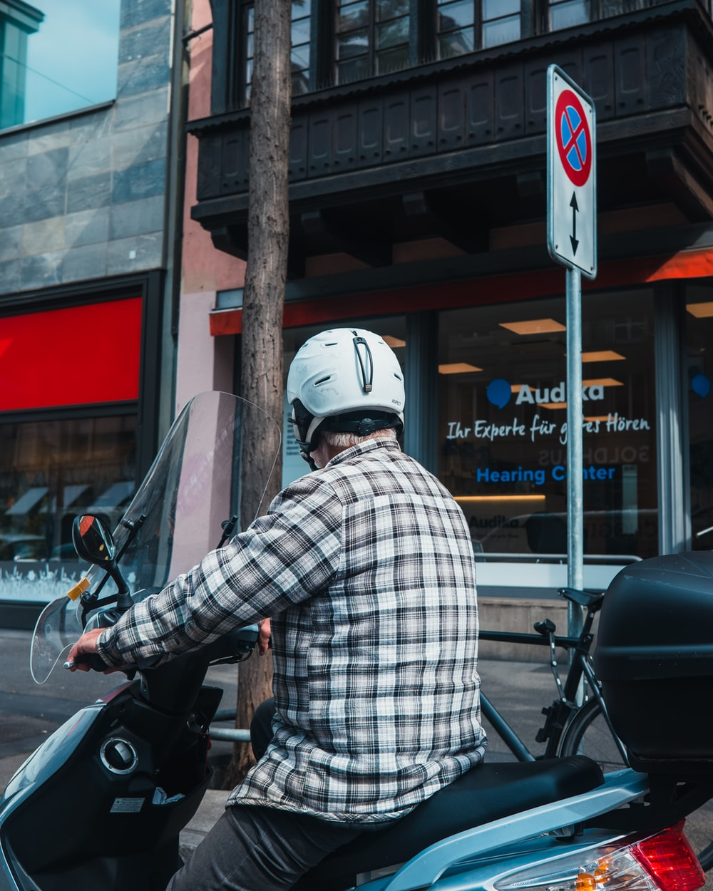 man in white and blue plaid dress shirt riding motorcycle