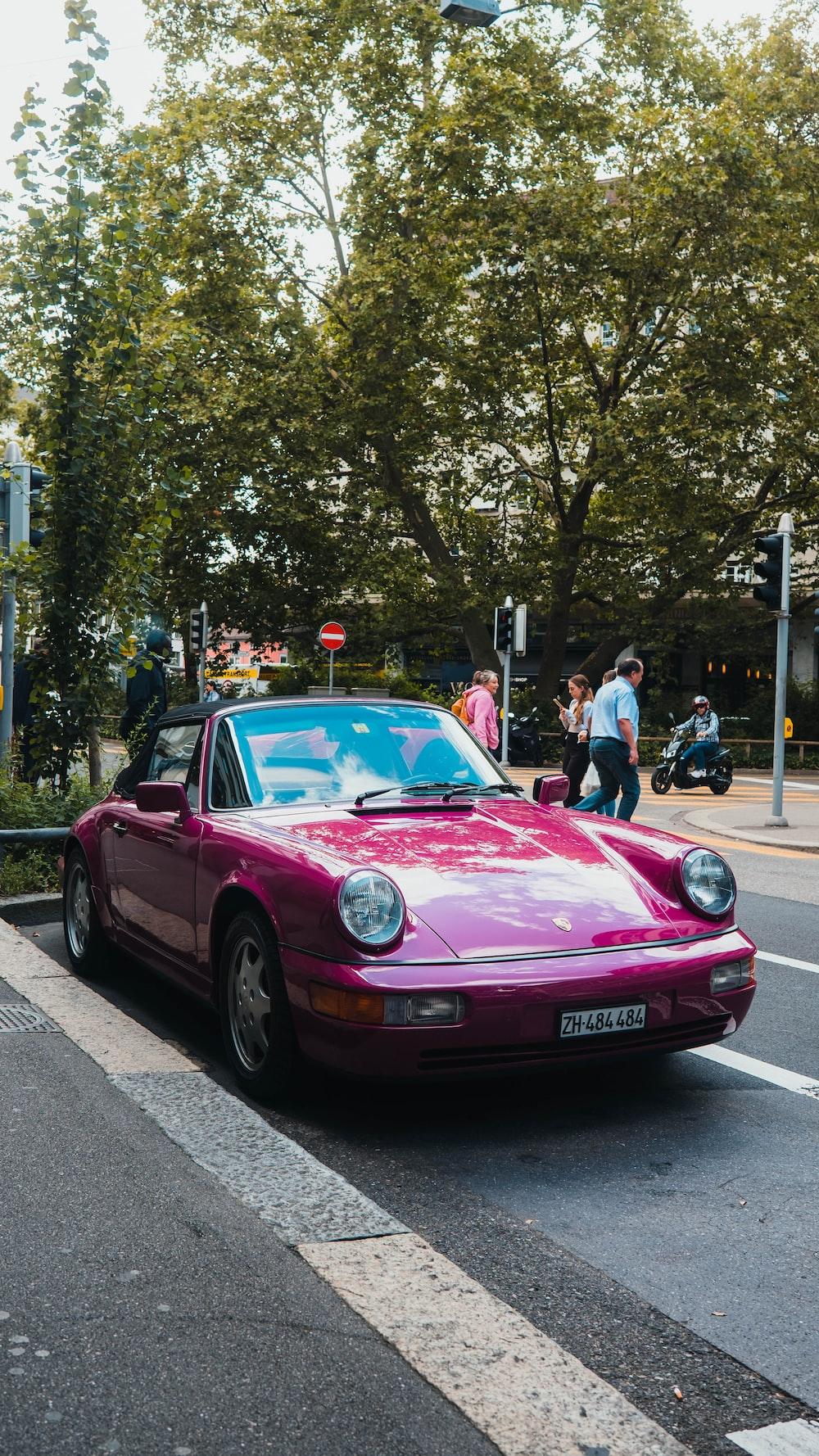 pink porsche 911 parked on street during daytime