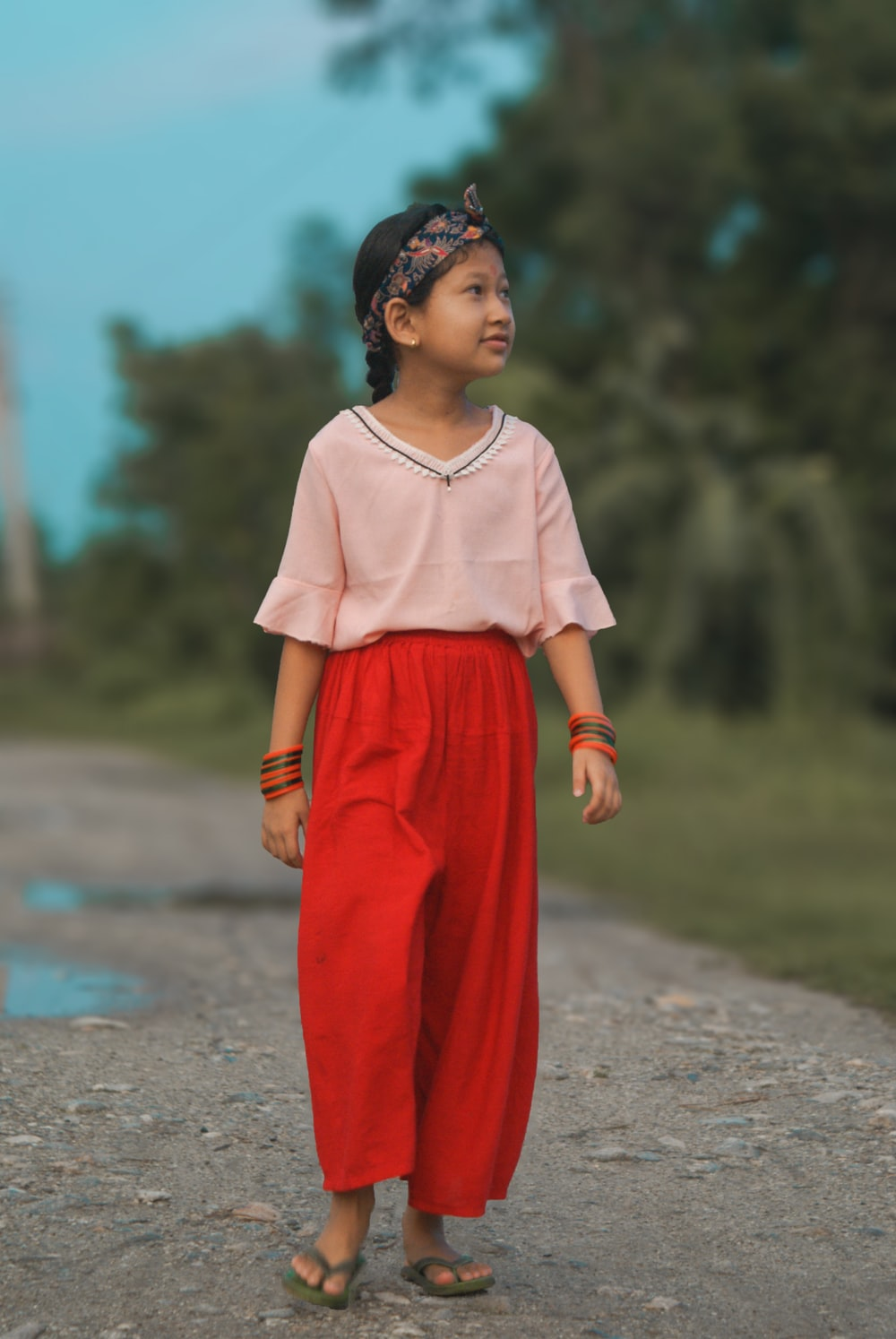 woman in pink dress standing on road during daytime
