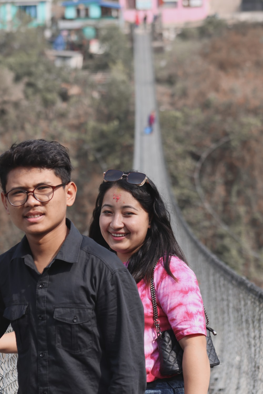 man in black button up shirt beside woman in pink jacket