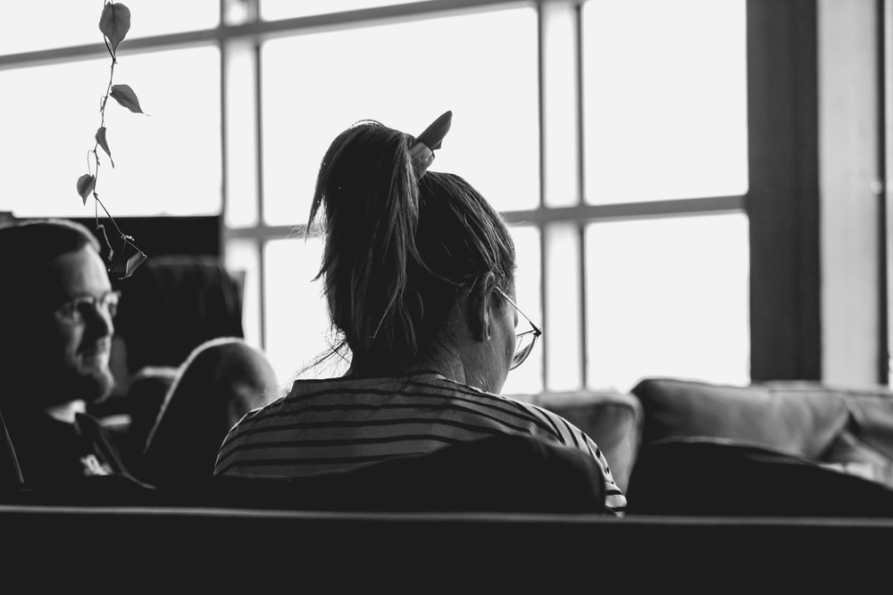 grayscale photo of woman sitting on sofa