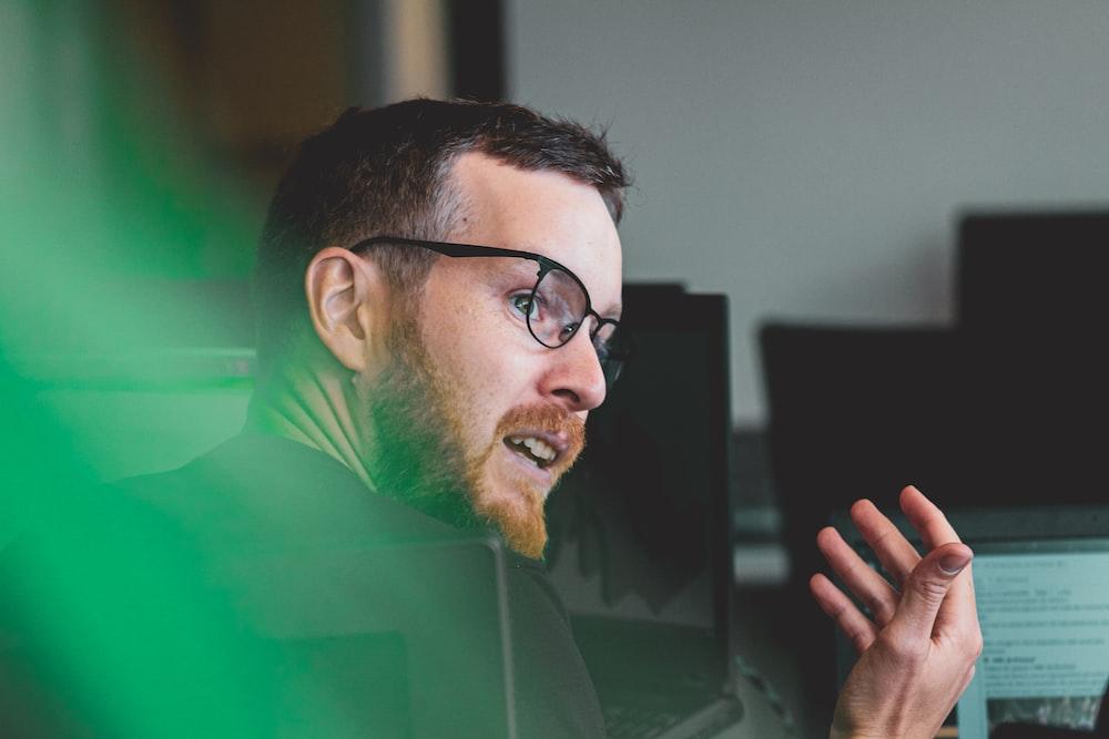 man in green shirt wearing black framed eyeglasses
