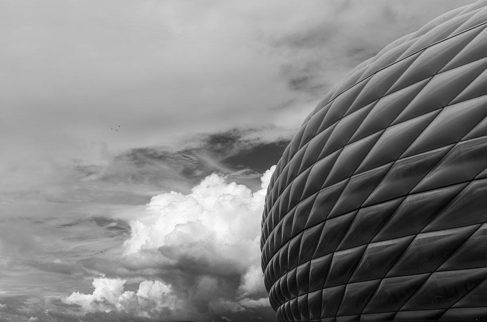 grayscale photo of clouds over building