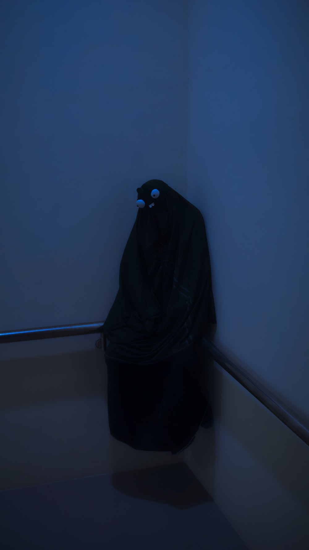 person in black robe standing beside white wall