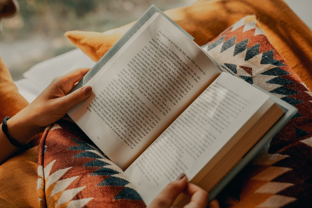 person reading book on brown and beige textile