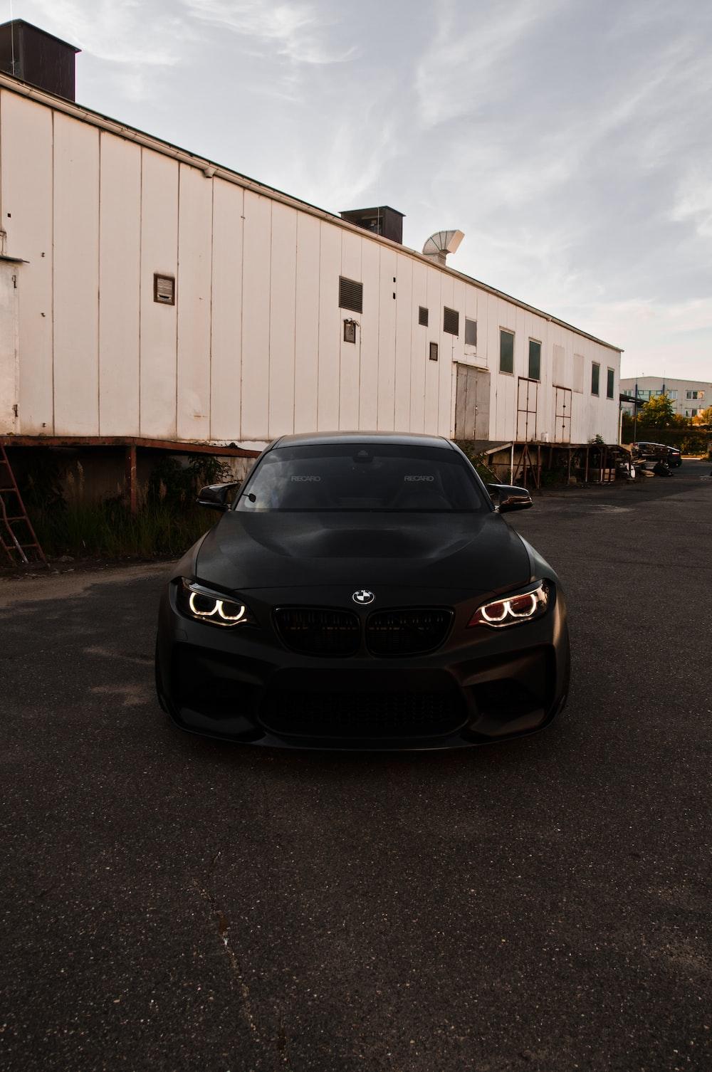 black bmw car parked near white garage during daytime