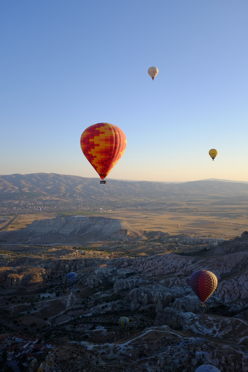 hot air balloons flying over the mountains during daytime
