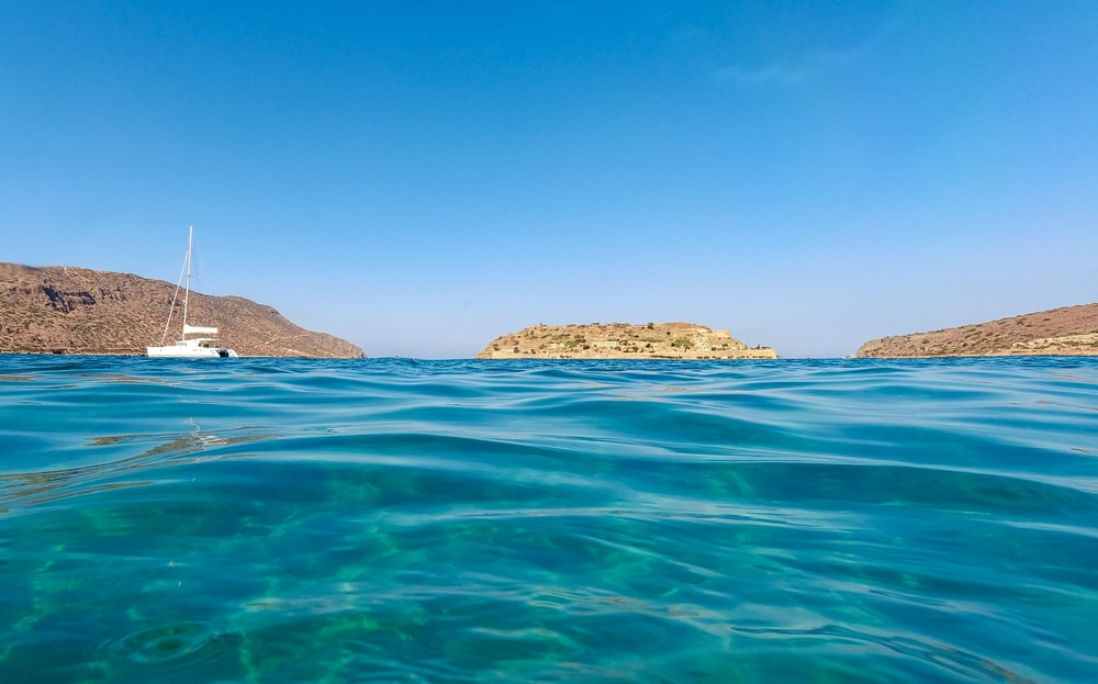 brown and green island on blue sea under blue sky during daytime