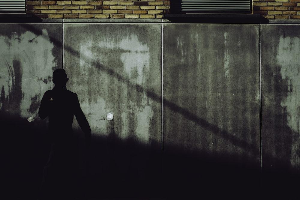 silhouette of man standing beside brick wall