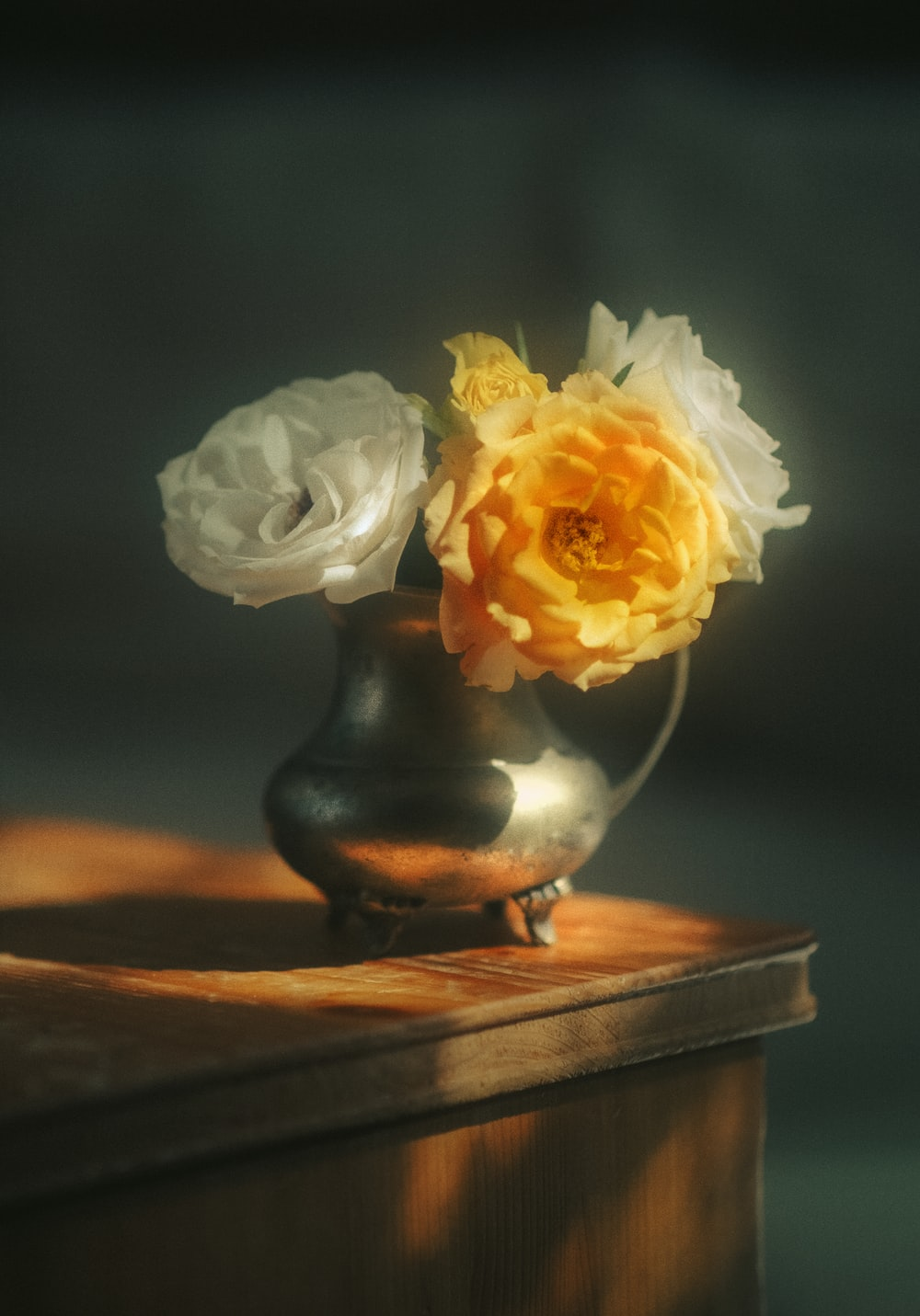 white and yellow flower on black ceramic vase