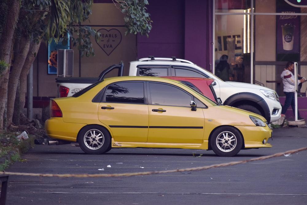 yellow sedan on gray asphalt road during daytime