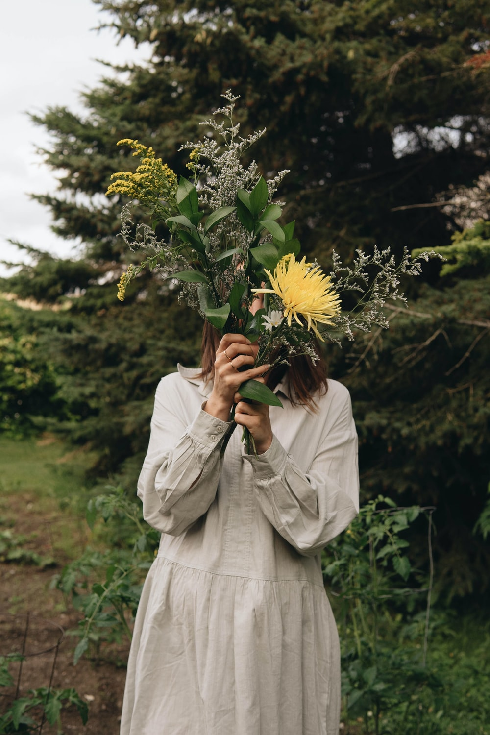 woman in white dress holding sunflower