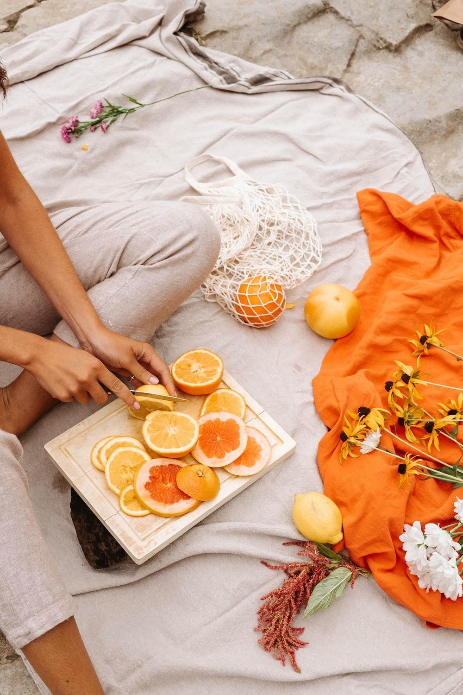 person holding orange fruit on white ceramic plate