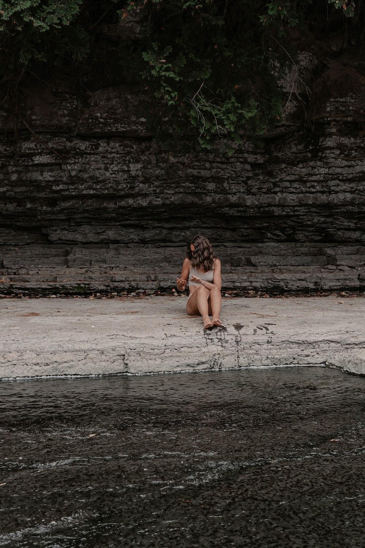 woman in black bikini sitting on white plastic chair