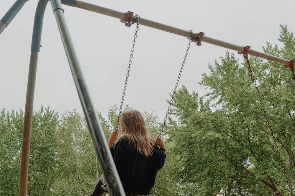 woman in black jacket sitting on swing