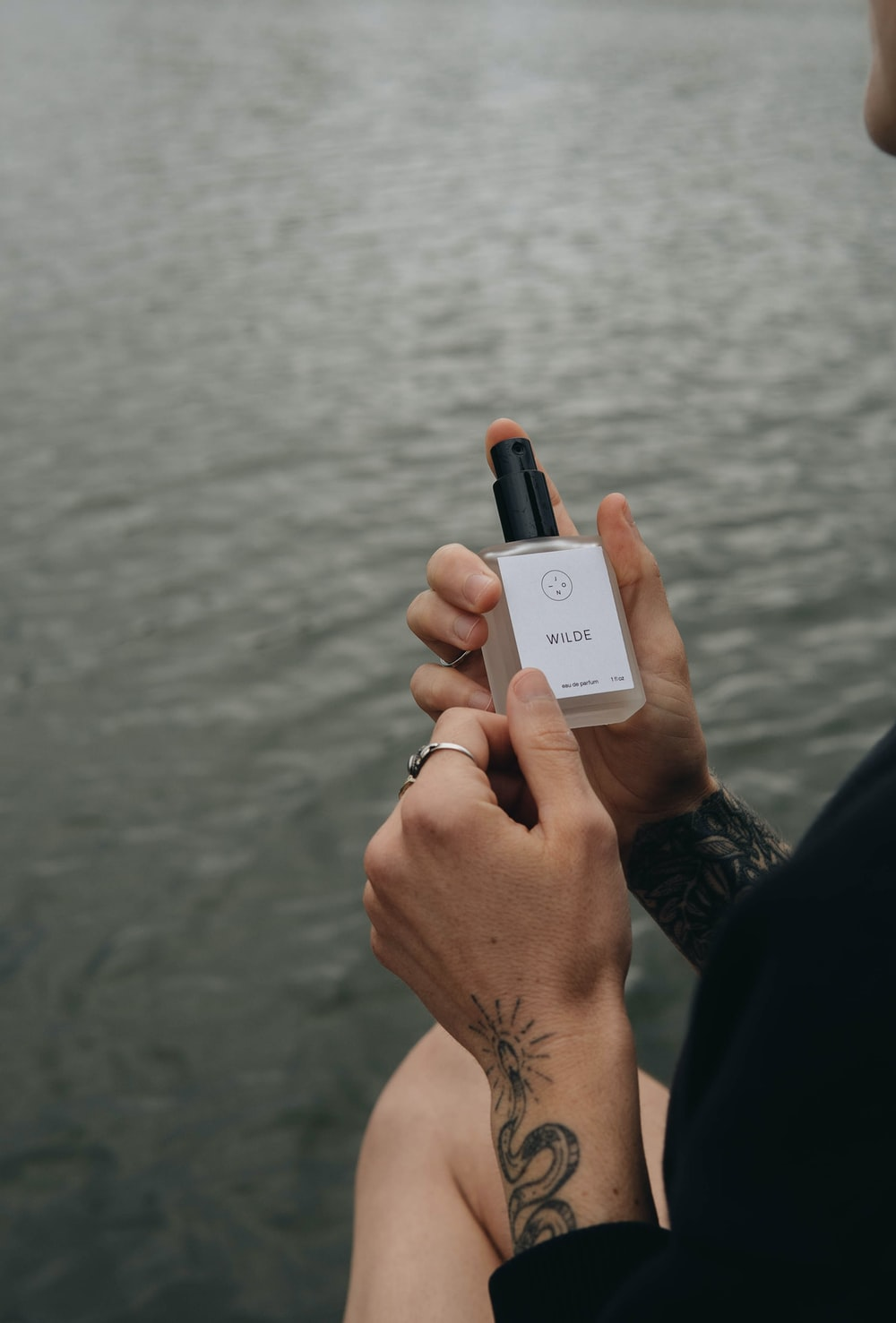 person holding white and black bottle