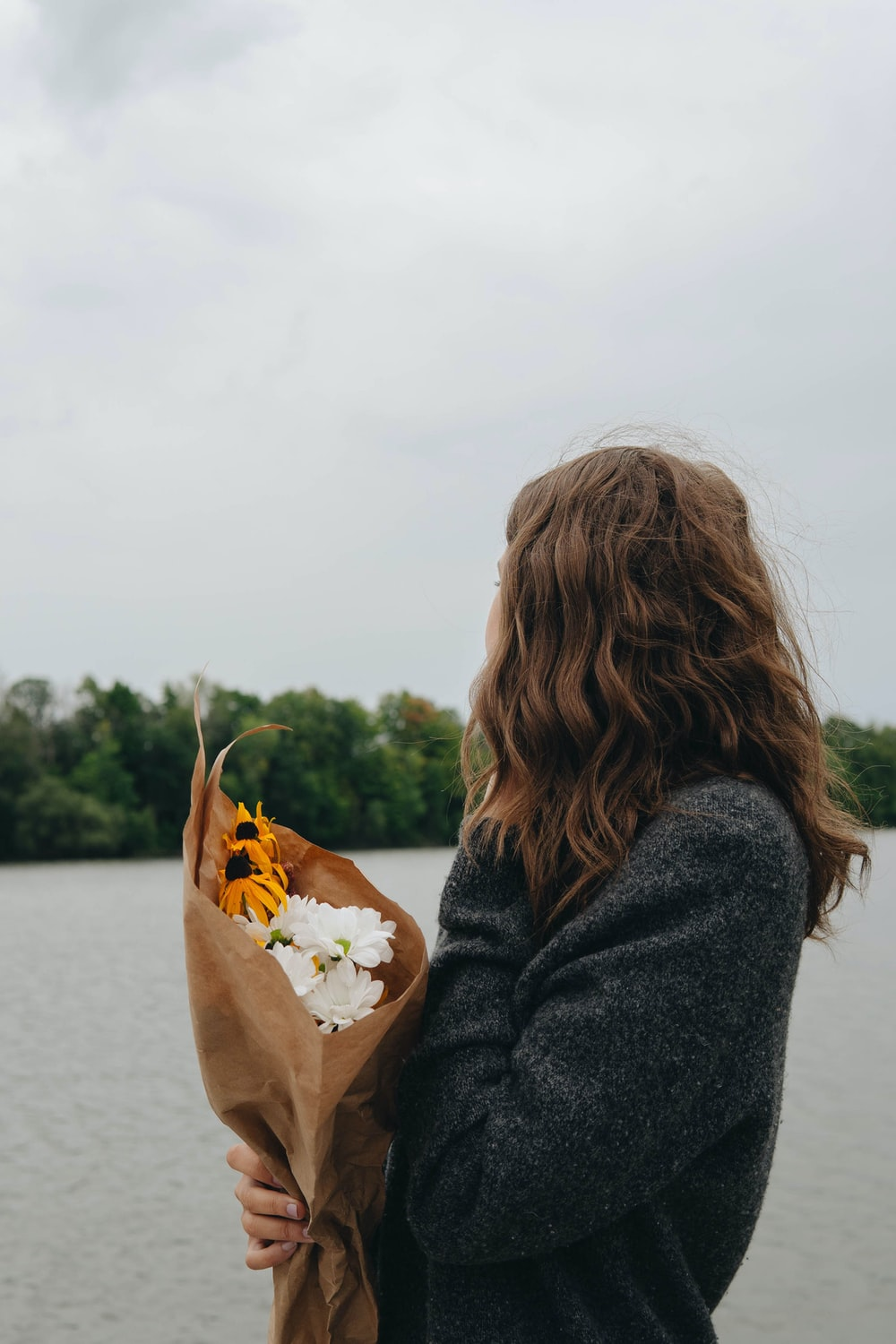 woman in black coat holding yellow leaf