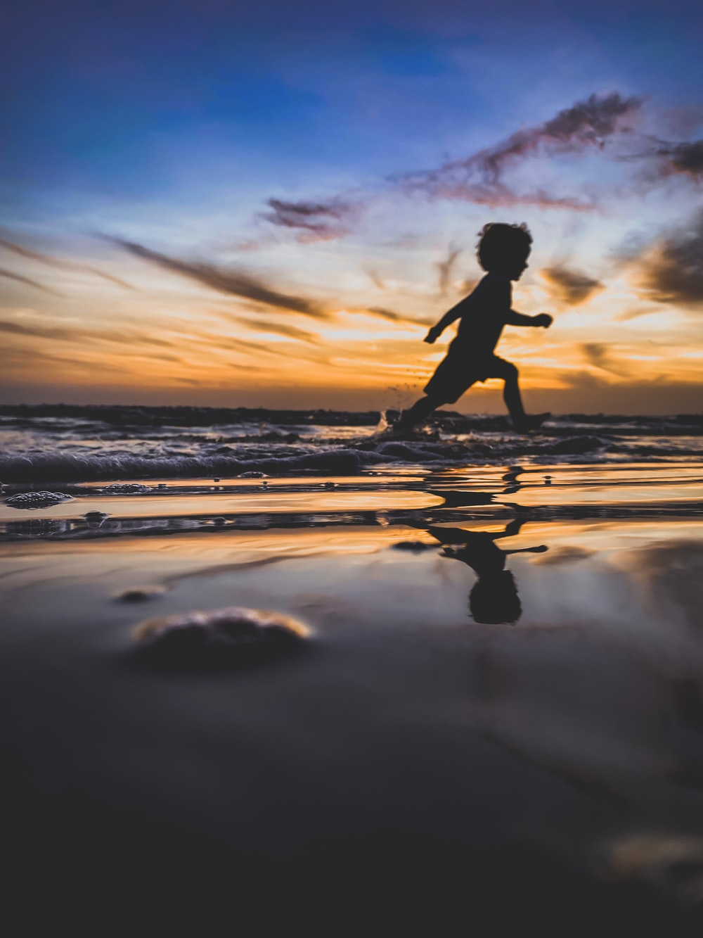 silhouette of woman running on beach during sunset