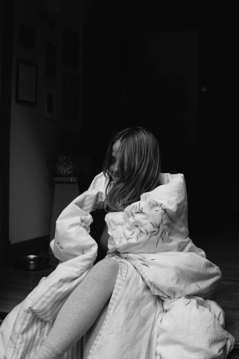 grayscale photo of woman in white hoodie sitting on chair