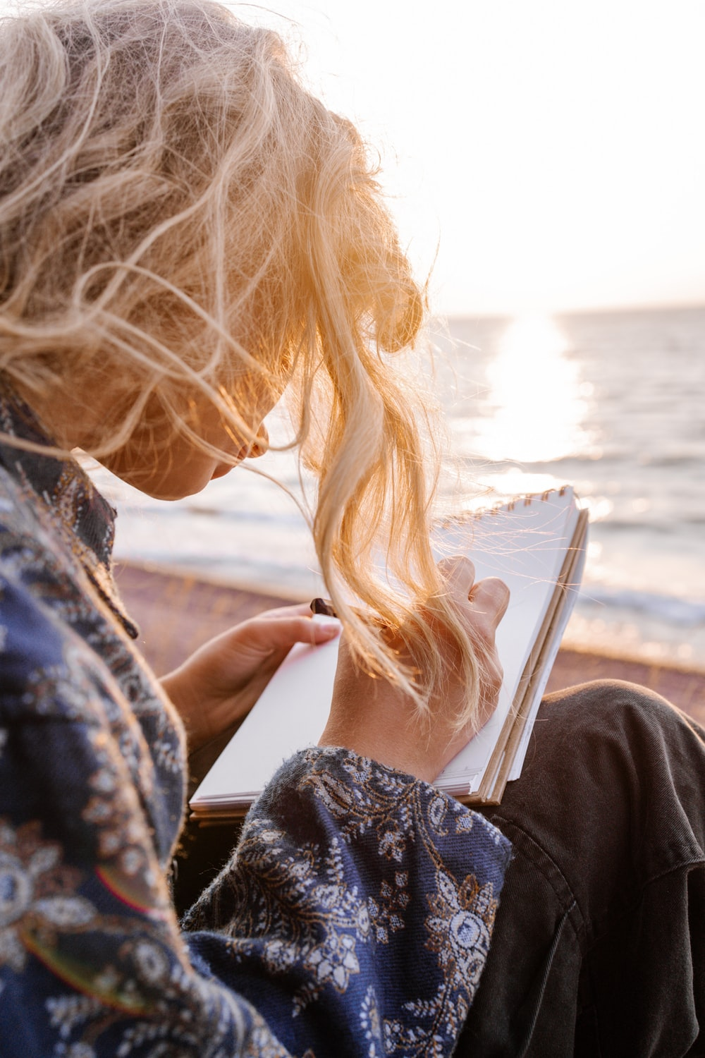 woman in blue and white floral shirt holding book near body of water during daytime
