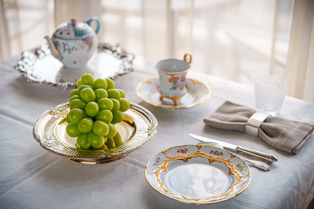green grapes on white and blue floral ceramic plate