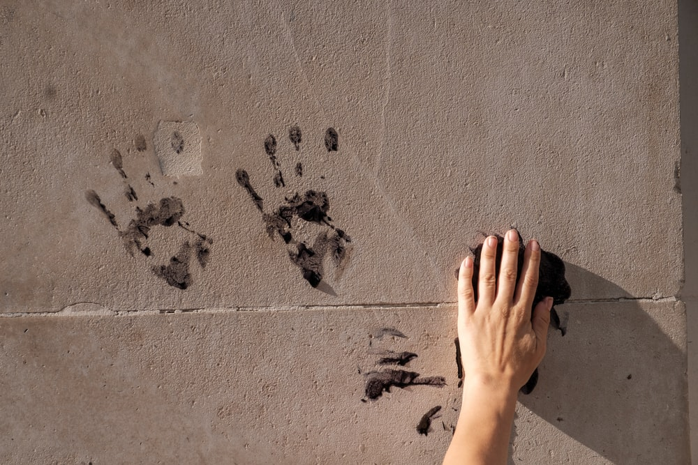 persons hand on gray concrete wall with black and white paint