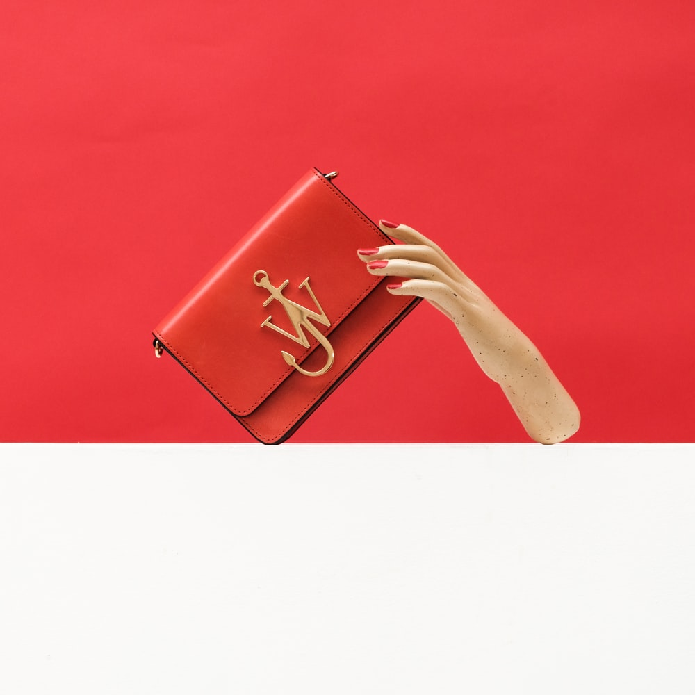 person holding pink leather wallet
