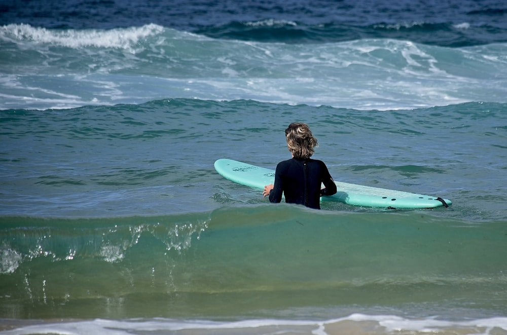 woman in black wet suit surfing on sea waves during daytime