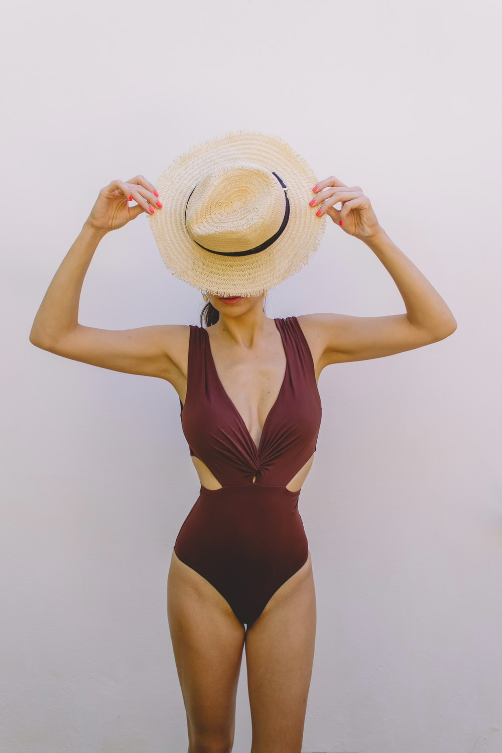 woman in brown one piece swimsuit wearing brown sun hat