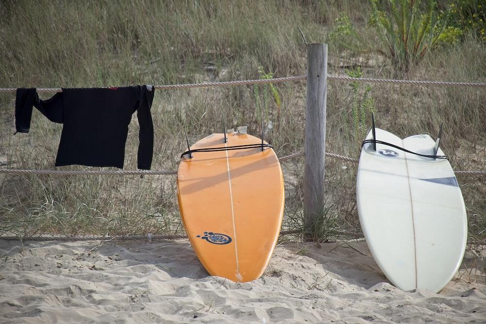 orange and white kayak on brown sand during daytime