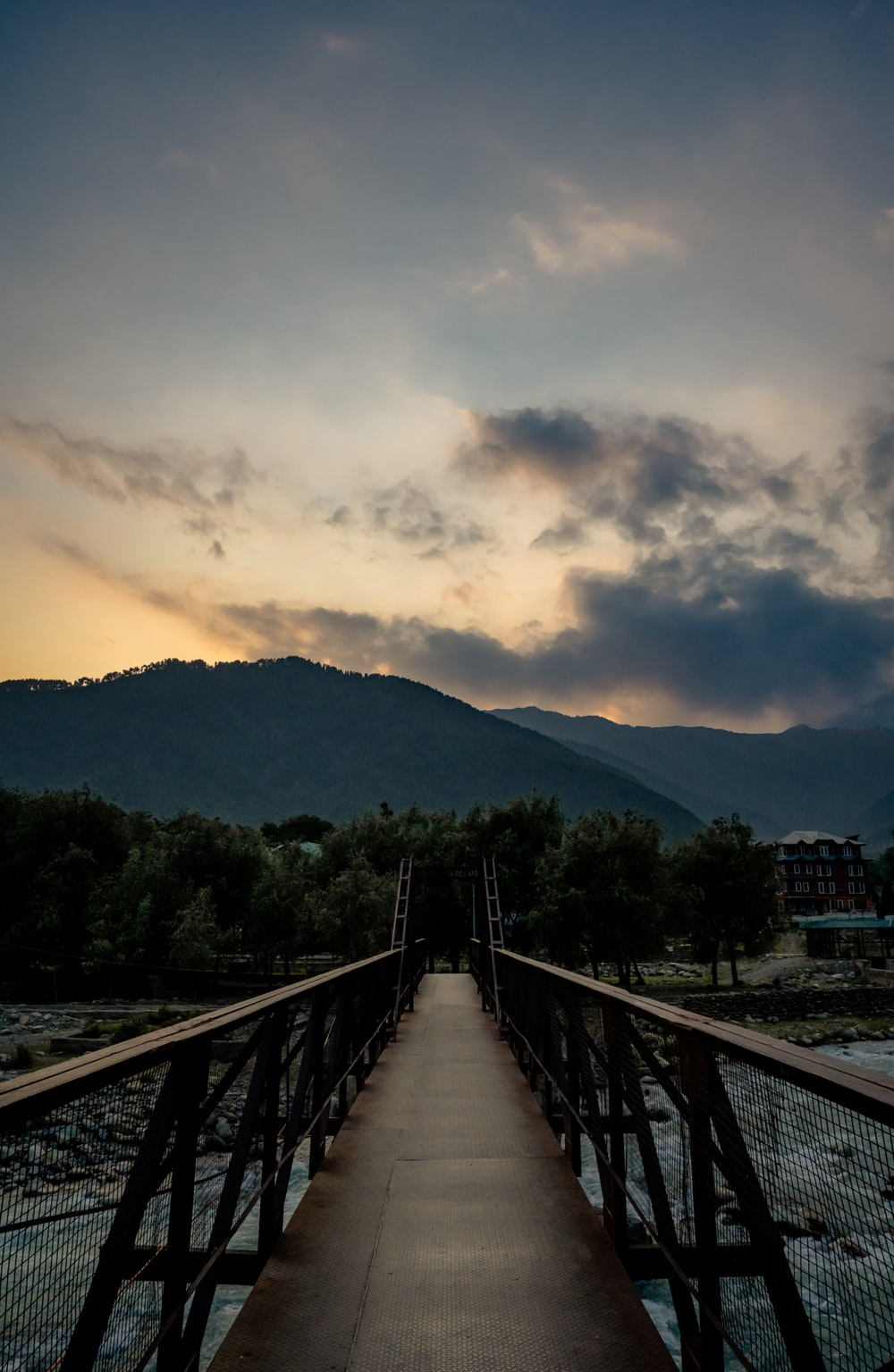 brown wooden bridge over the mountain during daytime