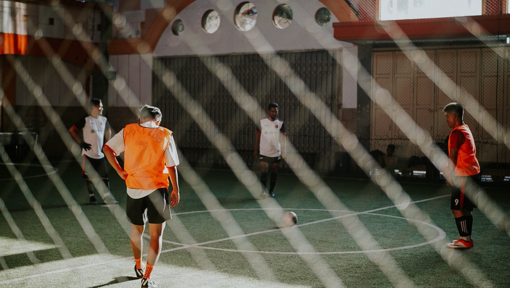 man in orange and white jersey shirt and black shorts standing on green and white tennis