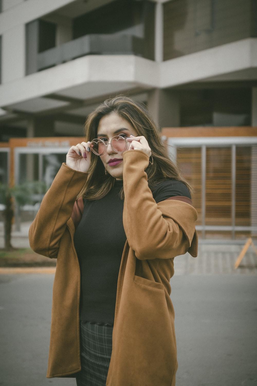 woman in brown coat holding her eyeglasses