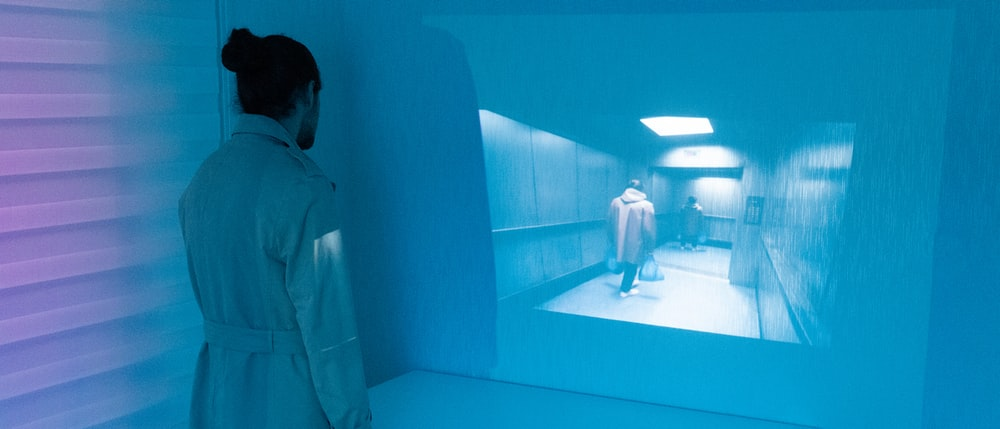 man in gray robe standing beside blue wall