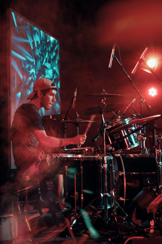 man in black shirt playing drum set