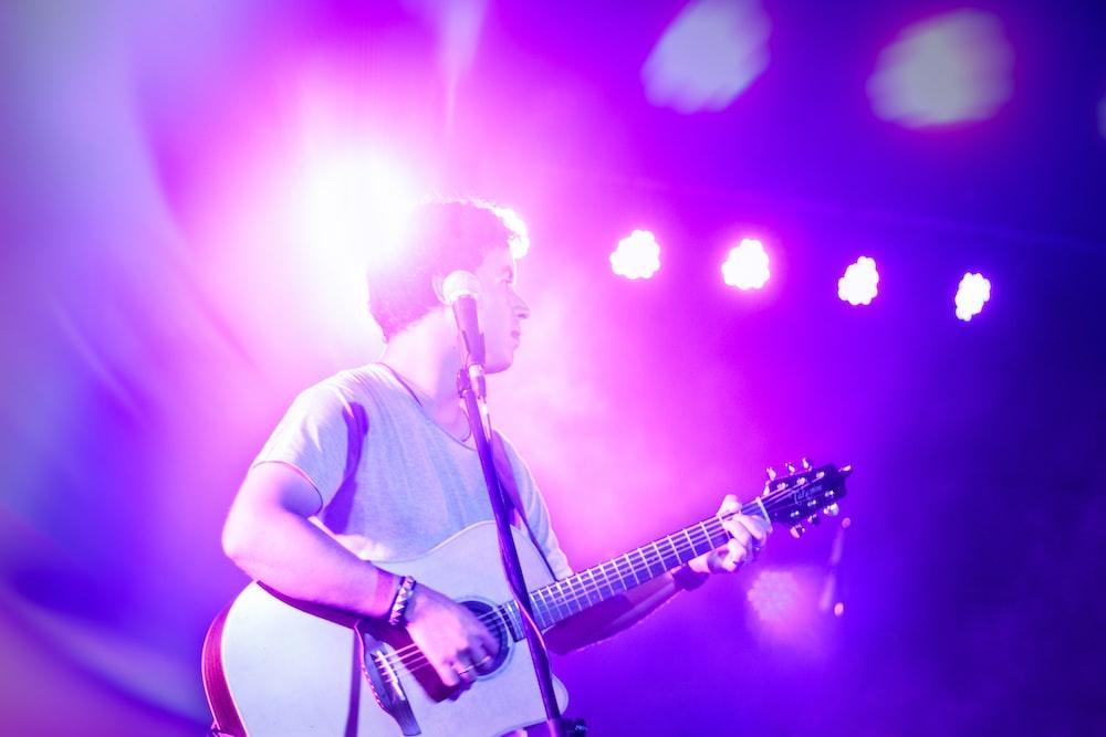 man in white t-shirt singing on stage