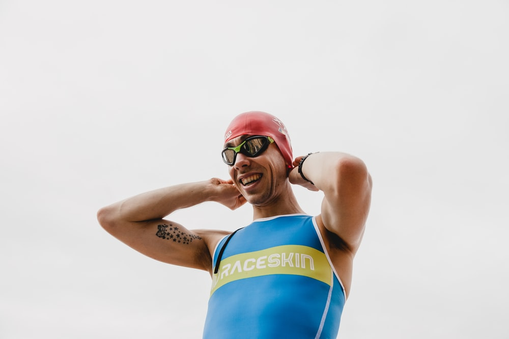 woman in blue and yellow tank top wearing red goggles