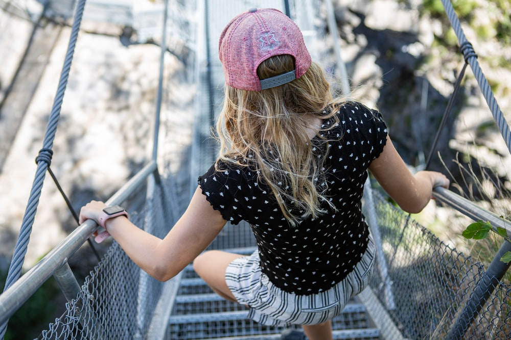 woman in black and white polka dot shirt and pink knit cap standing near gray metal