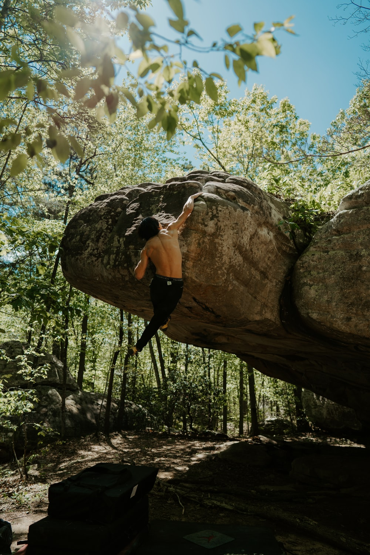 woman in black tank top and black leggings climbing on brown rock during daytime