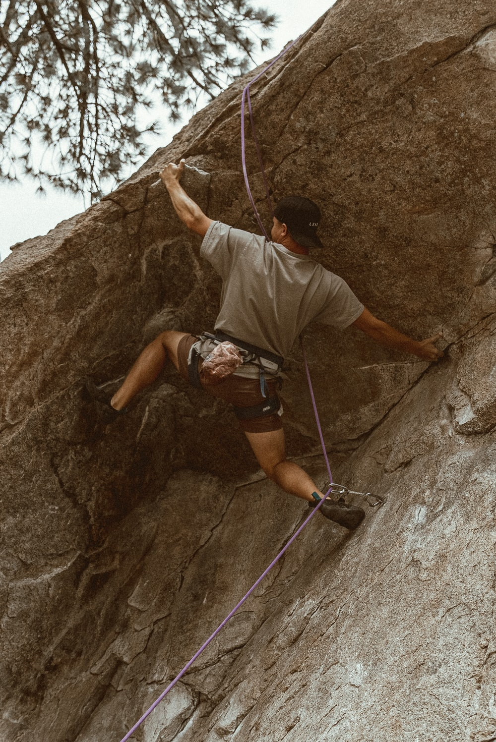 man in white t-shirt climbing on rocky mountain during daytime